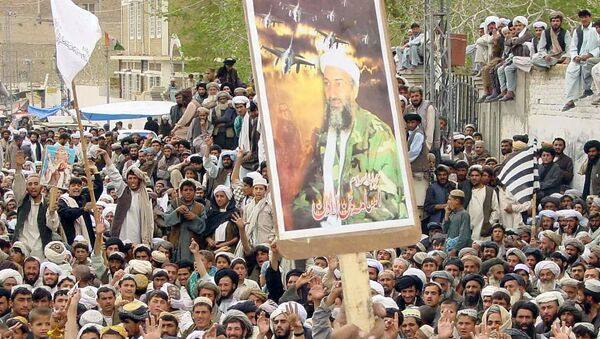 A protester raises US most wanted Osama bin Laden, Chief of al-Qaeda network portrait during an-anti US demonstration organised by a six Islamic parties alliance Muttahida Majlis-i-Amal (MMA) against the US-led forces military strike on Iraq, in southern city of Chaman close to the Afghanistan border, 21 March 2003.  - Sputnik International