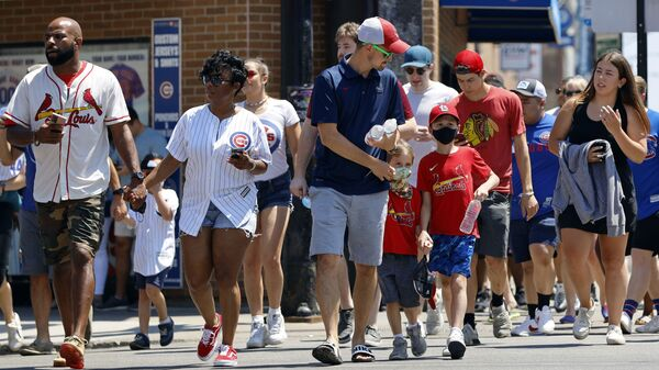 FILE - In this June 11, 2021, file photo, people cross a street as they make their way toward Chicago's Wrigley Field for a baseball game. COVID-19 deaths in the U.S. have dipped below 300 a day for the first time since the early days of the disaster in March 2020, while the number of Americans fully vaccinated has reached about 150 million - Sputnik International