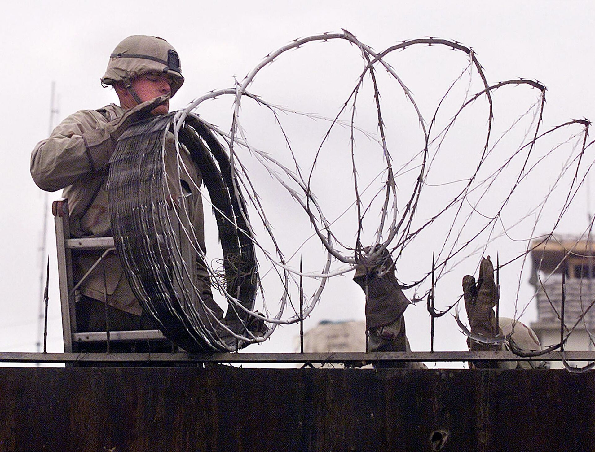 In this file photo a US Marine is given a hand using barbed wire to secure the walls the US embassy in Kabul on January 11, 2002. - The United States said on August 12, 2021 it was sending troops to the international airport in Afghanistan's capital Kabul to pull out US embassy staff as the Taliban makes rapid gains.We are further reducing our civilian footprint in Kabul in light of the evolving security situation, State Department spokesman Ned Price told reporters.This president prioritizes above all else the safety and security of Americans who are serving overseas, he said of Joe Biden, who has ordered a withdrawal of US troops from Afghanistan after nearly 20 years. - Sputnik International, 1920, 07.09.2021