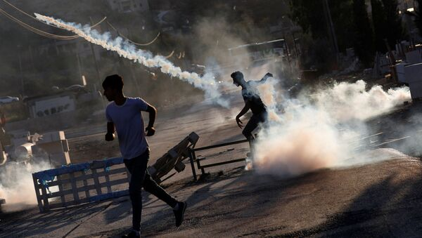 Palestinian protester throws back a tear gas grenade during a protest over the killing of a Palestinian man by Israeli soldiers, according to health ministry, in Beita in the Israeli-occupied West Bank July 28, 2021 - Sputnik International