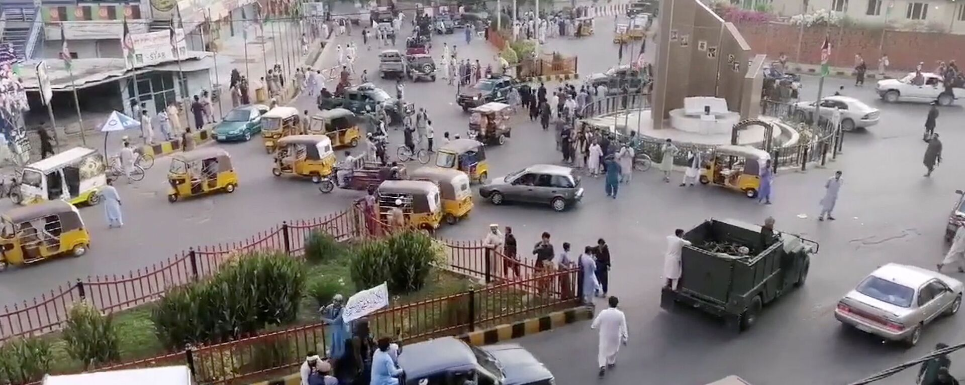 Taliban militants waving a Taliban flag on the back of a pickup truck drive past a crowded street at Pashtunistan Square area in Jalalabad, Afghanistan in this still image taken from social media video uploaded on August 15, 2021. Social media website/via REUTERS THIS IMAGE HAS BEEN SUPPLIED BY A THIRD PARTY. - Sputnik International, 1920