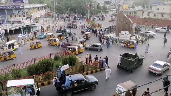 Taliban militants waving a Taliban flag on the back of a pickup truck drive past a crowded street at Pashtunistan Square area in Jalalabad, Afghanistan in this still image taken from social media video uploaded on August 15, 2021. Social media website/via REUTERS THIS IMAGE HAS BEEN SUPPLIED BY A THIRD PARTY. - Sputnik International
