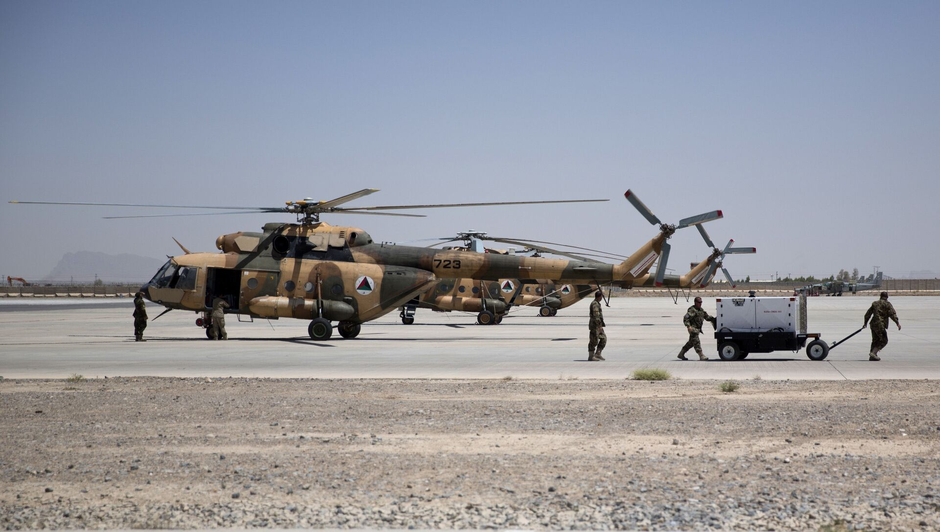 Members of Afghanistan's National Army work near military helicopters, in Kandahar Air Field, Afghanistan, Tuesday, Aug. 18, 2015. Since the departure from Afghanistan last year of most international combat troops, Afghan security forces have been fighting the insurgency alone. Figures show that casualty rates are extremely high, reflecting an emboldened Taliban testing the commitment and strength of the Afghan military. (AP Photo/Massoud Hossaini) - Sputnik International, 1920, 15.08.2021