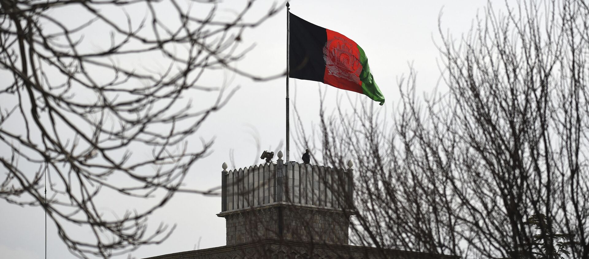 An Afghan security personnel keeps watch on a tower as the Afghan national flag flutters ahead of the start of Afghanistan President Ashraf Ghani's swearing-in inauguration ceremony, at the Presidential Palace in Kabul on March 9, 2020. - Sputnik International, 1920