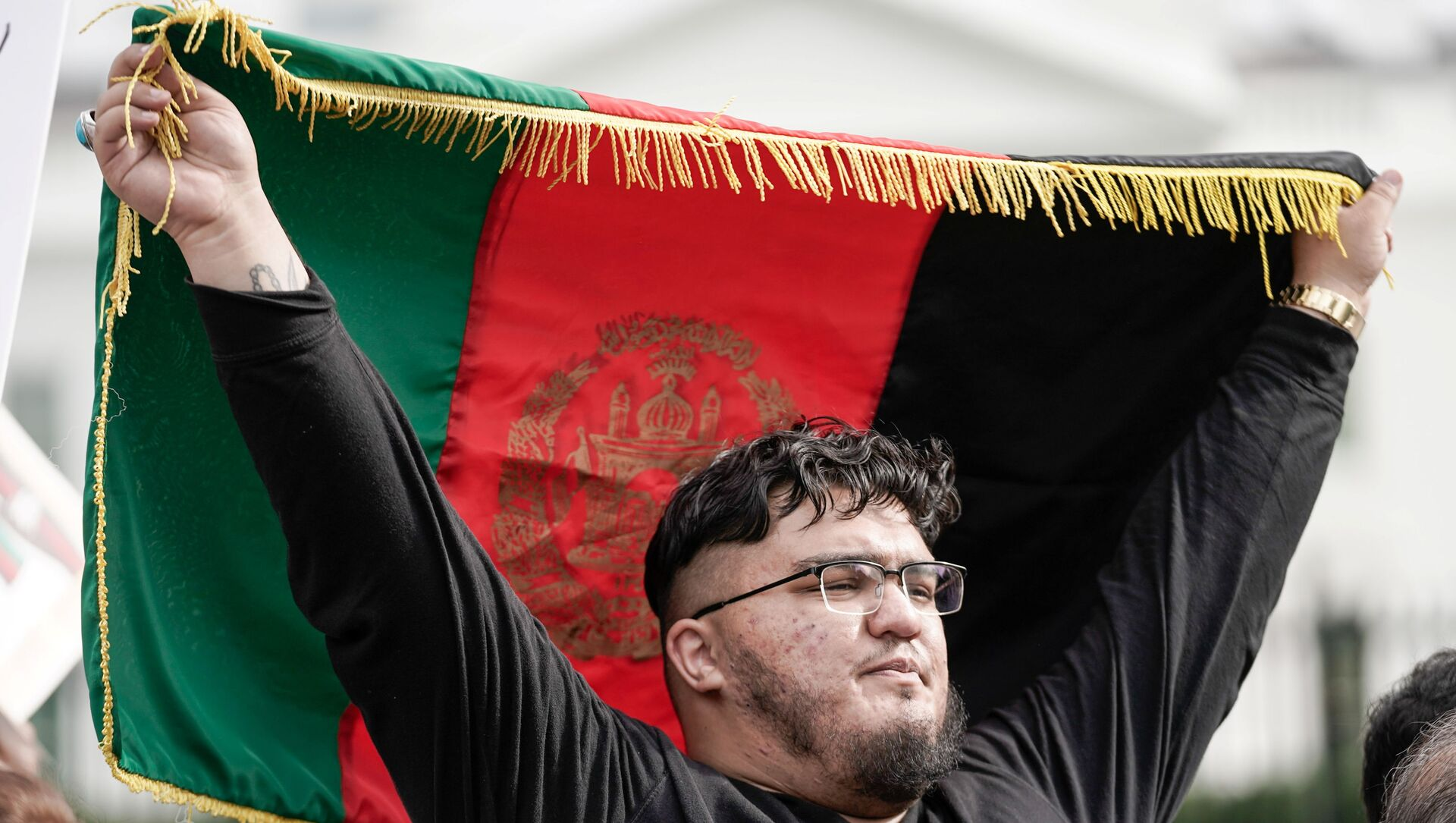 A man holds Afghanistan's flag, as demonstrators shout Peace in Afghanistan and hold up signs as they gather in front of the White House in Washington, U.S., August 15, 2021 on the day Taliban insurgents entered Afghanistan's capital Kabul.   - Sputnik International, 1920, 15.08.2021