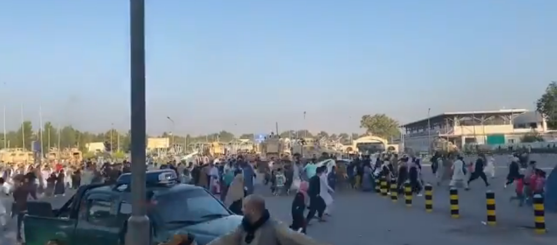 Screenshot from a video allegedly showing a crowd of people rushing to the Kabul international airport as gunshots are heard - Sputnik International, 1920