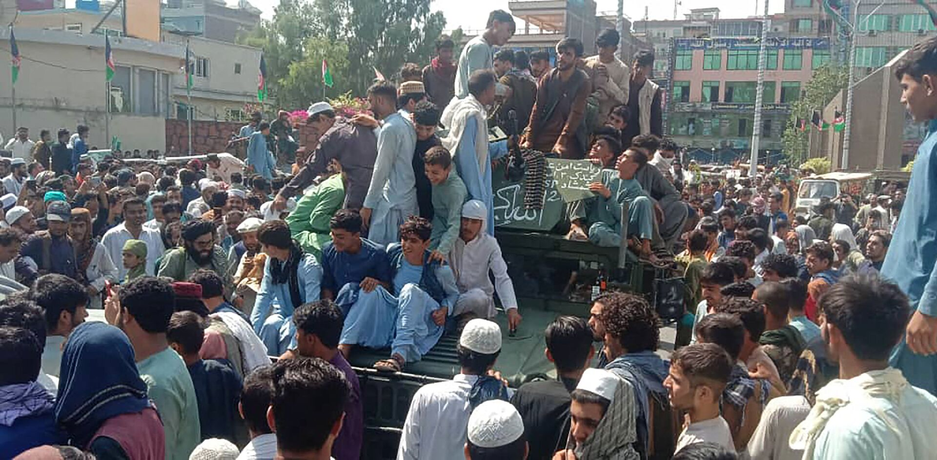 Taliban fighters and local people sit on an Afghan National Army (ANA) Humvee vehicle on a street in Jalalabad province on August 15, 2021.  - Sputnik International, 1920, 07.09.2021