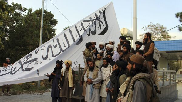 Taliban fighters poses for a photograph while raising their flag Taliban fighters raise their flag at the Ghazni provincial governor's house, in Ghazni, southeastern, Afghanistan, Sunday, Aug. 15, 2021.  - Sputnik International