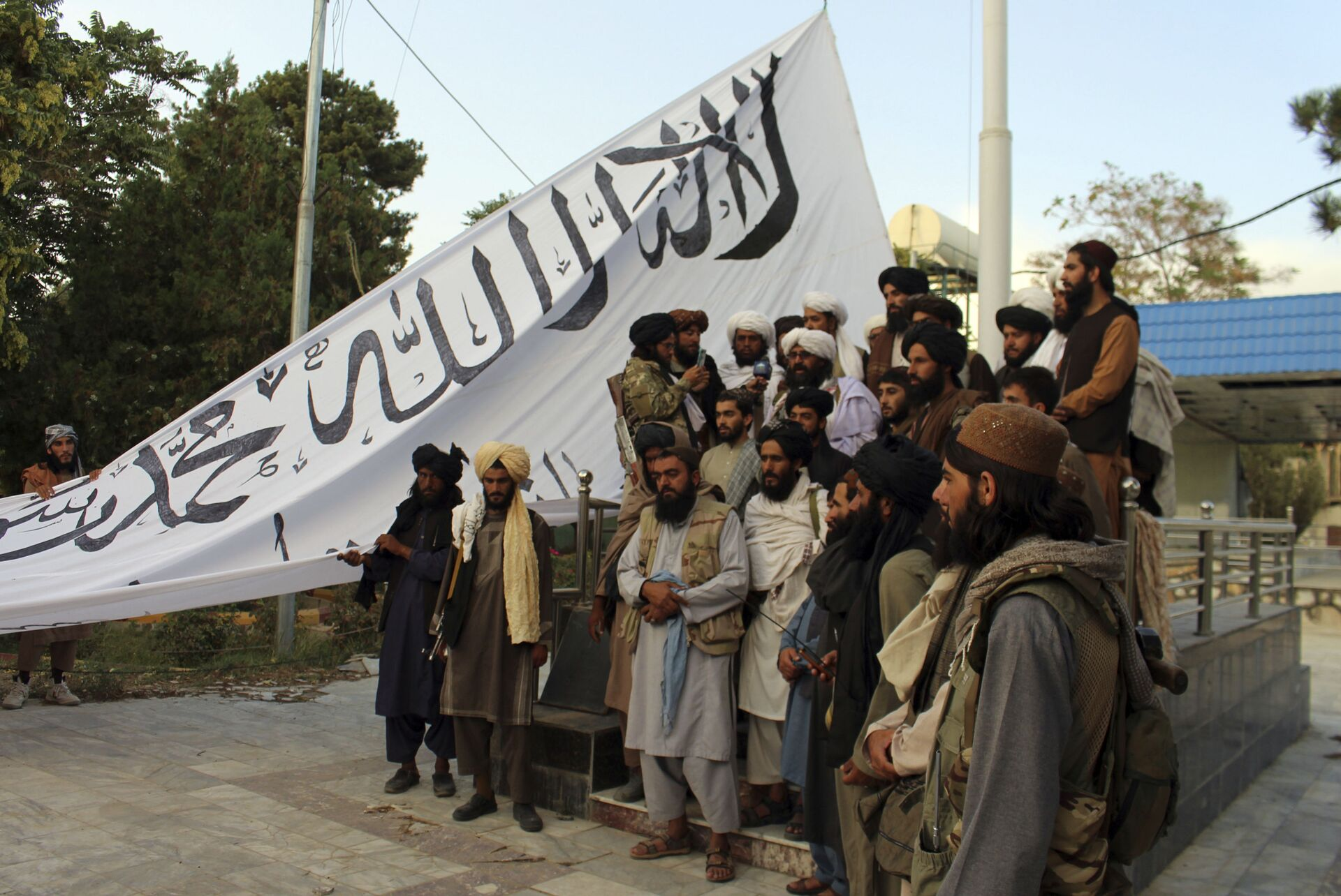 Taliban fighters poses for a photograph while raising their flag Taliban fighters raise their flag at the Ghazni provincial governor's house, in Ghazni, southeastern, Afghanistan, Sunday, Aug. 15, 2021.  - Sputnik International, 1920, 07.09.2021