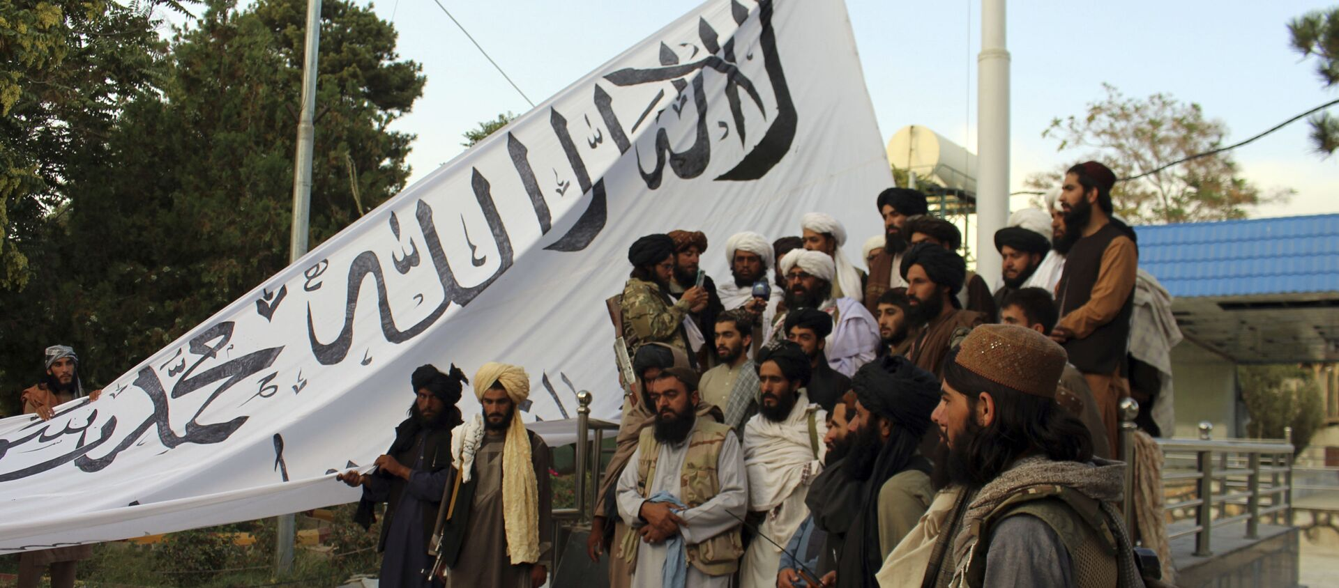 Taliban fighters poses for a photograph while raising their flag Taliban fighters raise their flag at the Ghazni provincial governor's house, in Ghazni, southeastern, Afghanistan, Sunday, Aug. 15, 2021.  - Sputnik International, 1920, 16.08.2021