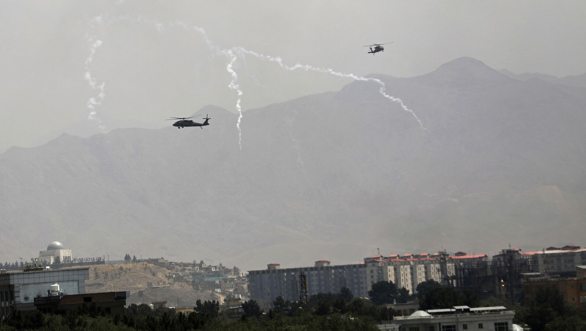 Anti-missile decoy flares are deployed as U.S. Black Hawk military helicopters and a dirigible balloon fly over the city of Kabul, Afghanistan, Sunday, Aug. 15, 2021. - Sputnik International, 1920, 22.08.2021