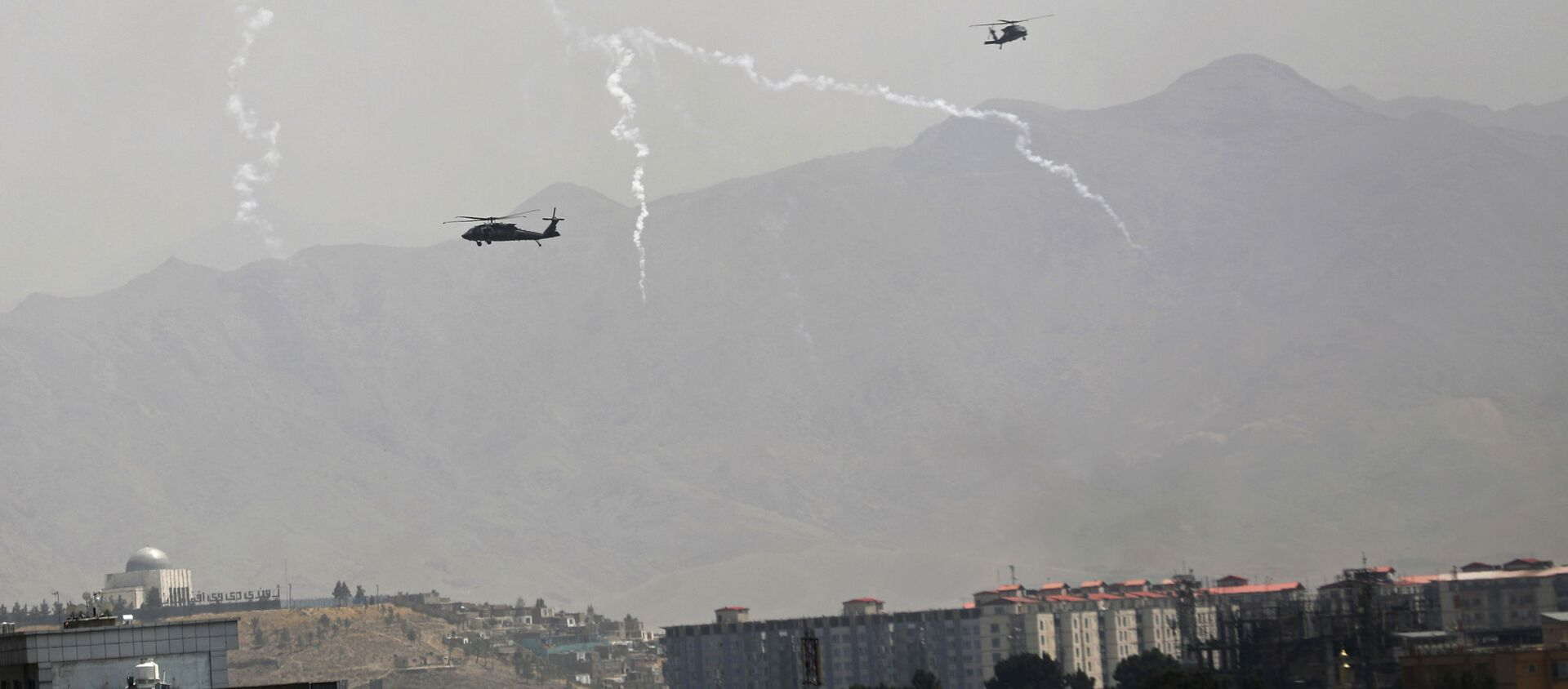 Anti-missile decoy flares are deployed as U.S. Black Hawk military helicopters and a dirigible balloon fly over the city of Kabul, Afghanistan, Sunday, Aug. 15, 2021. - Sputnik International, 1920
