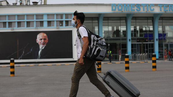 A passenger walks to the departures terminal of Hamid Karzai International Airport, in Kabul, Afghanistan, Saturday, Aug. 14, 2021. - Sputnik International