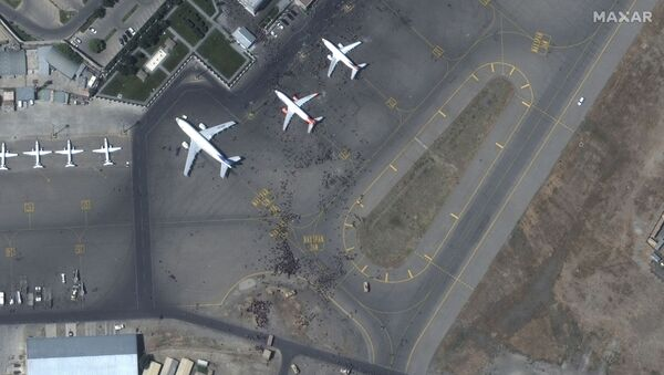 This handout satellite image released by Maxar Technologies shows crowds of people on the tarmac, during the chaotic scene underway at Kabul's Hamid Karzai International Airport in Afghanistan as thousands of people converged on the tarmac and airport runways as countries attempt to evacuate personnel from the city on August 16, 2021. - Sputnik International