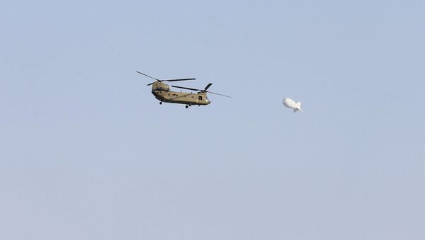 A blimp passes in the sky as a U.S. Army Chinook helicopter flies over Kabul, Afghanistan August 15, 2021. - Sputnik International