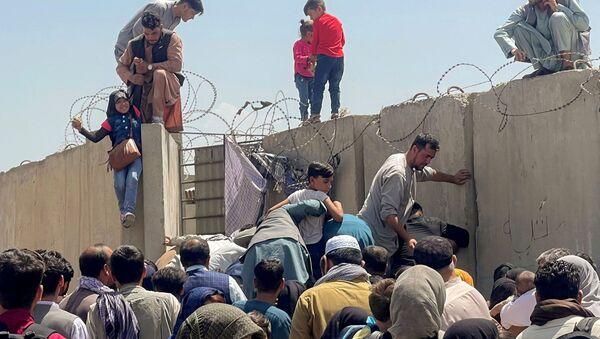 A man pulls a girl to get inside Hamid Karzai International Airport in Kabul, Afghanistan August 16, 2021. - Sputnik International