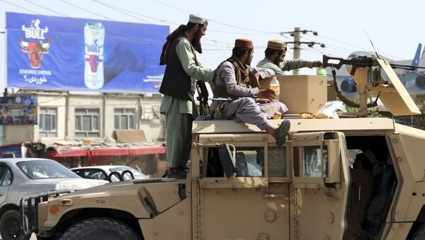 Taliban fighters stand guard in front of the Hamid Karzai International Airport, in Kabul, Afghanistan, Monday, Aug. 16, 2021. - Sputnik International
