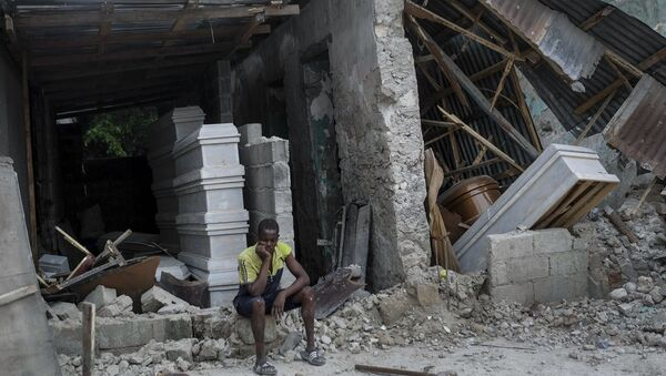 A man sits in front of a collapsed funeral home in Les Cayes, Haiti, Monday, Aug. 16, 2021, two days after a 7.2-magnitude earthquake struck the southwestern part of the country. - Sputnik International