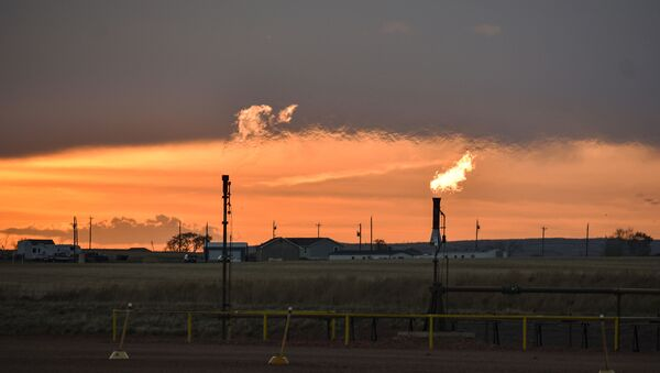 In this Tuesday, May 18, 2021, photo, flares burn natural gas from oil production in the Fort Berthold Indian Reservation east of New Town, North Dakota. - Sputnik International