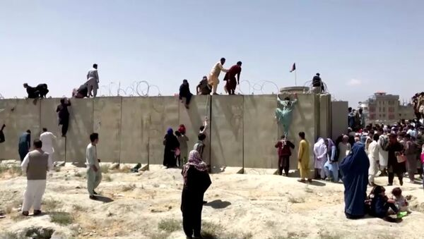 People climb a barbed wire wall to enter the airport in Kabul, Afghanistan August 16, 2021, in this still image taken from a video - Sputnik International