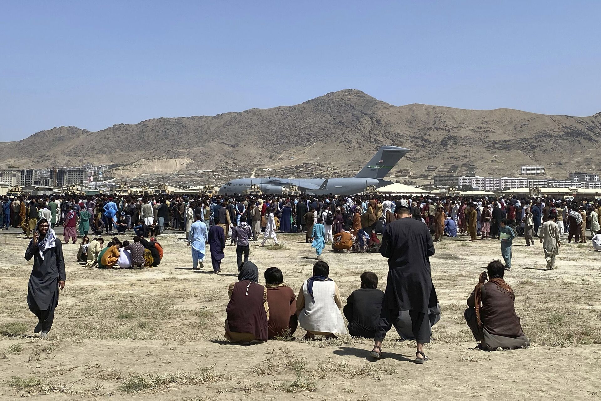 Hundreds of people gather near a U.S. Air Force C-17 transport plane at a perimeter at the international airport in Kabul, Afghanistan, Monday, Aug. 16, 2021 - Sputnik International, 1920, 07.09.2021