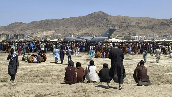Hundreds of people gather near a U.S. Air Force C-17 transport plane at a perimeter at the international airport in Kabul, Afghanistan, Monday, Aug. 16, 2021 - Sputnik International