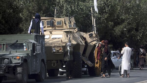 Taliban fighters stand guard on the road to the Hamid Karzai International Airport, in Kabul, Afghanistan, Monday, Aug. 16, 2021 - Sputnik International