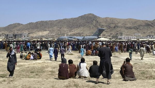 Hundreds of people gather near a U.S. Air Force C-17 transport plane at a perimeter at the international airport in Kabul, Afghanistan, Monday, Aug. 16, 2021. On Monday, the U.S. military and officials focus was on Kabul's airport, where thousands of Afghans trapped by the sudden Taliban takeover rushed the tarmac and clung to U.S. military planes deployed to fly out staffers of the U.S. Embassy, which shut down Sunday, and others - Sputnik International