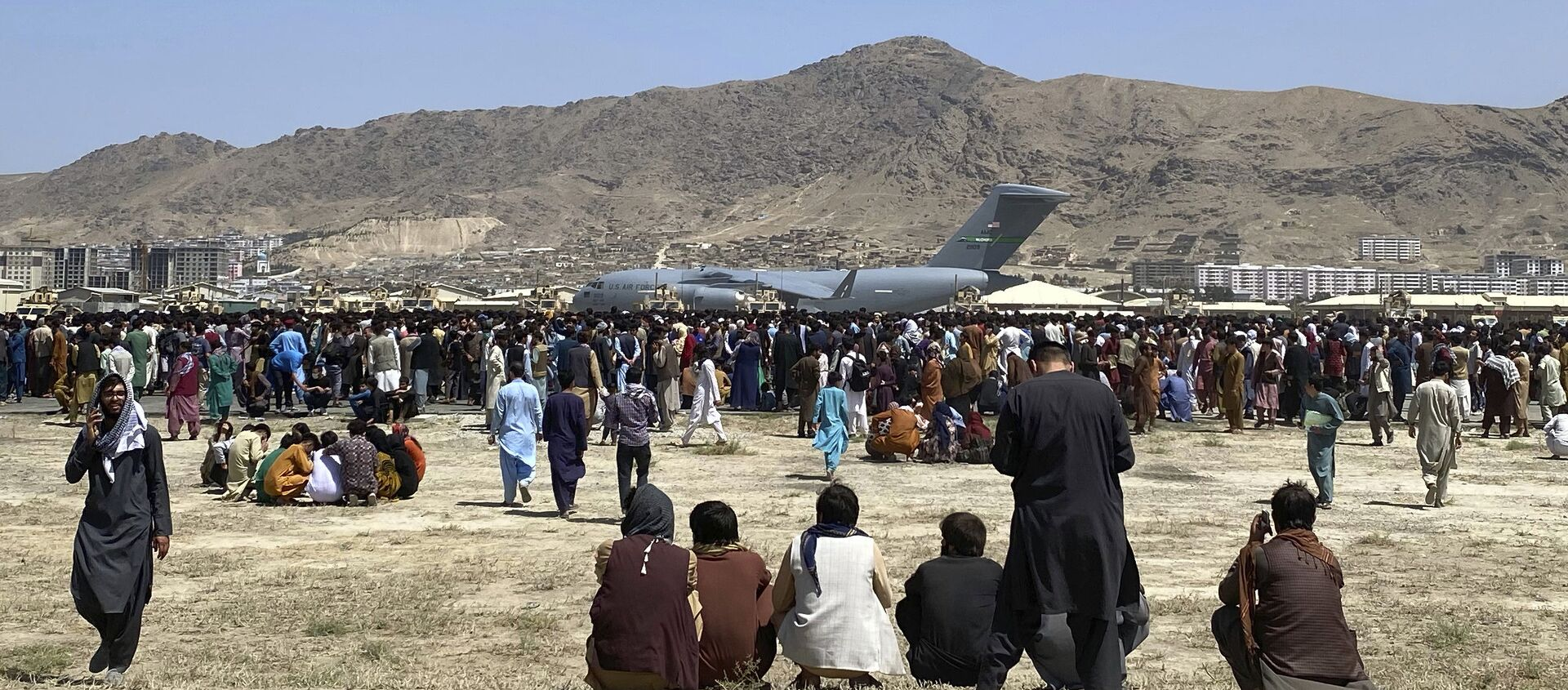 Hundreds of people gather near a U.S. Air Force C-17 transport plane at a perimeter at the international airport in Kabul, Afghanistan, Monday, Aug. 16, 2021. On Monday, the U.S. military and officials focus was on Kabul's airport, where thousands of Afghans trapped by the sudden Taliban takeover rushed the tarmac and clung to U.S. military planes deployed to fly out staffers of the U.S. Embassy, which shut down Sunday, and others - Sputnik International, 1920