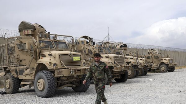 An Afghan army soldier walks past Mine Resistant Ambush Protected vehicles, MRAP, that were left after the American military left Bagram air base, in Parwan province north of Kabul, Afghanistan, Monday, July 5, 2021. - Sputnik International