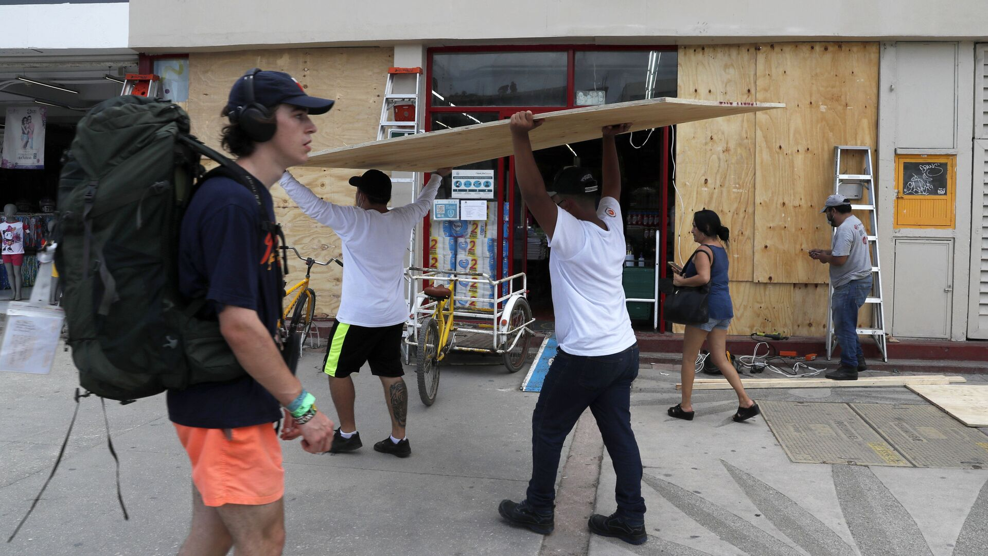 Workers cover shop windows with plywood in Tulum, Quintana Roo State, Mexico, Wednesday, Aug. 18, 2021. Residents and tourists along the Caribbean coast began making preparations for Grace, a storm that drenched Haiti and Jamaica and is now forecast to hit Mexico´s Yucatan peninsula like a hurricane early Thursday morning. - Sputnik International, 1920, 19.08.2021
