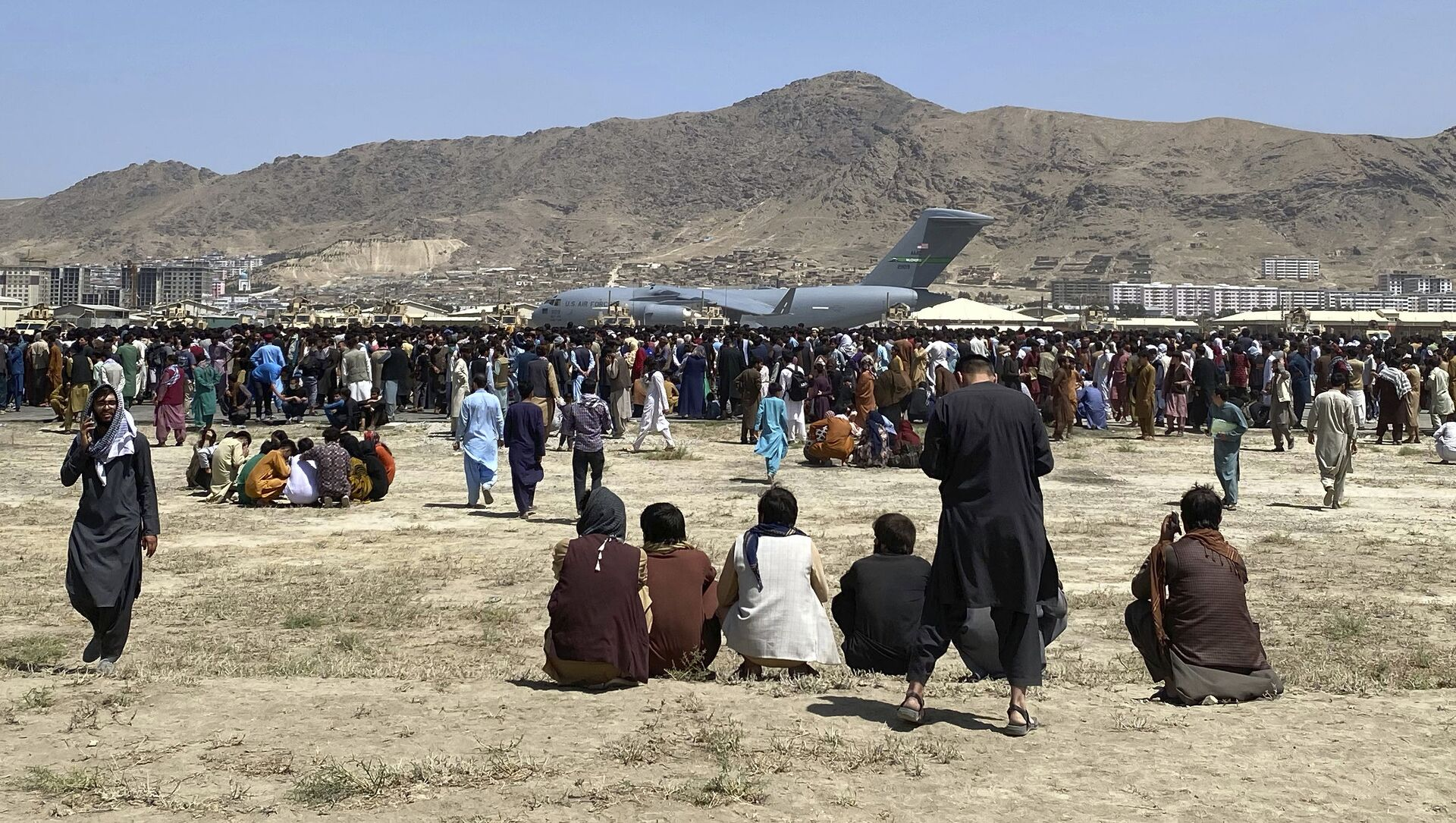 Hundreds of people gather near a U.S. Air Force C-17 transport plane at a perimeter at the international airport in Kabul, Afghanistan, Monday, Aug. 16, 2021. - Sputnik International, 1920, 26.08.2021