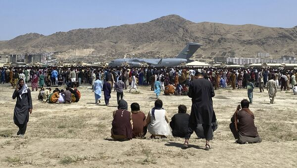 Hundreds of people gather near a US Air Force C-17 transport plane at a perimeter at the international airport in Kabul, Afghanistan, on Monday, 16 August 2021. - Sputnik International