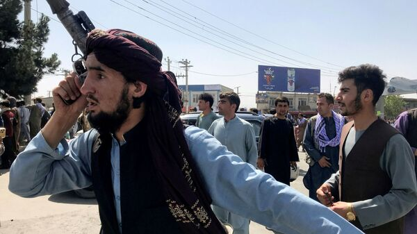 A member of the Taliban forces inspects the area outside Hamid Karzai International Airport in Kabul, Afghanistan, 16 August 2021 - Sputnik International