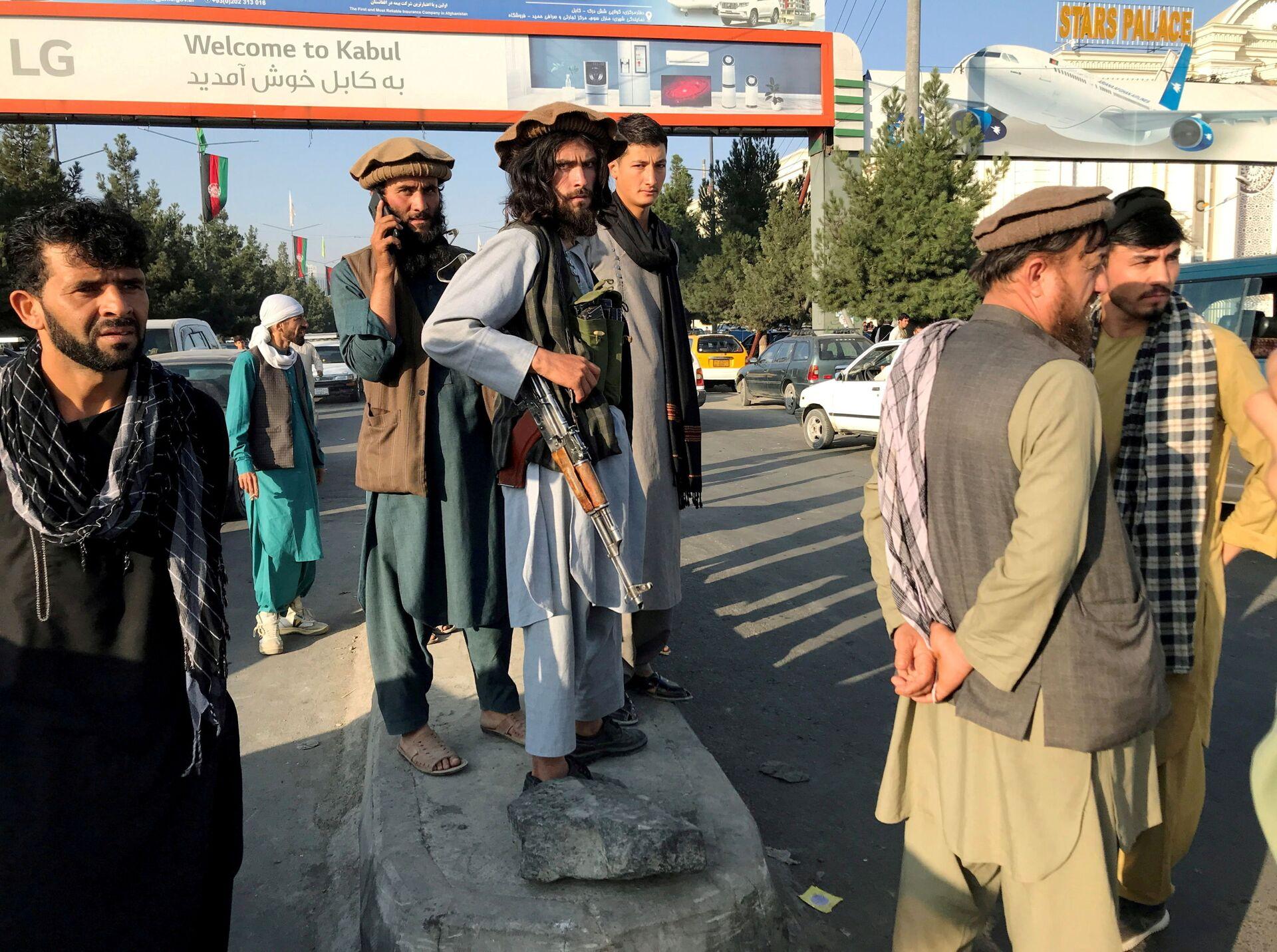 A member of Taliban (C) stands outside Hamid Karzai International Airport in Kabul, Afghanistan, August 16 - Sputnik International, 1920, 07.09.2021