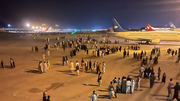 An undated amateur picture obtained by Reuters on August 19, 2021 shows people walking on the tarmac of the airport in Kabul, Afghanistan. - Sputnik International