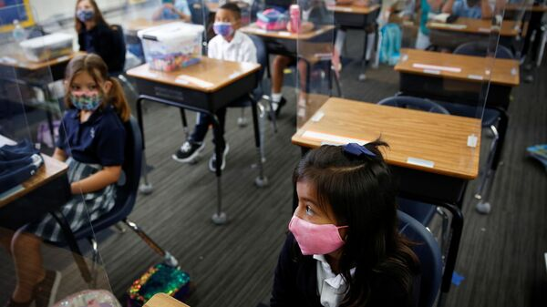 A student wearing a protective mask, attends class on the first day of school, amid the coronavirus disease (COVID-19) pandemic, at St. Lawrence Catholic School in North Miami Beach, Florida, U.S. August 18, 2021. - Sputnik International