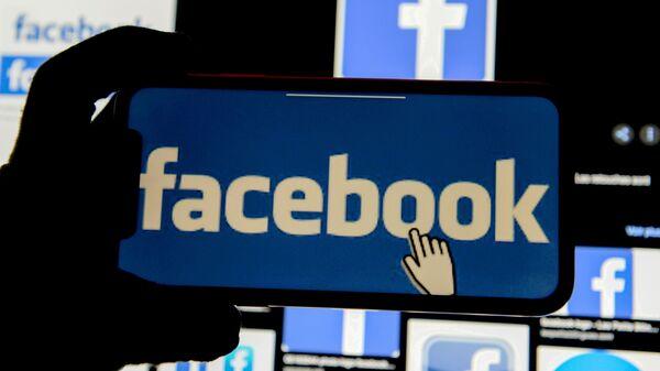 The Facebook logo is displayed on a mobile phone in this picture illustration taken 2 December 2019. - Sputnik International
