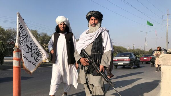 FILE PHOTO: A Taliban fighter holding an M16 assault rifle stands outside the Interior Ministry in Kabul, Afghanistan, 16 August 2021. - Sputnik International