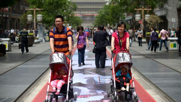 A couple pushes their young children in prams along a street in Beijing on May 19, 2013 - Sputnik International