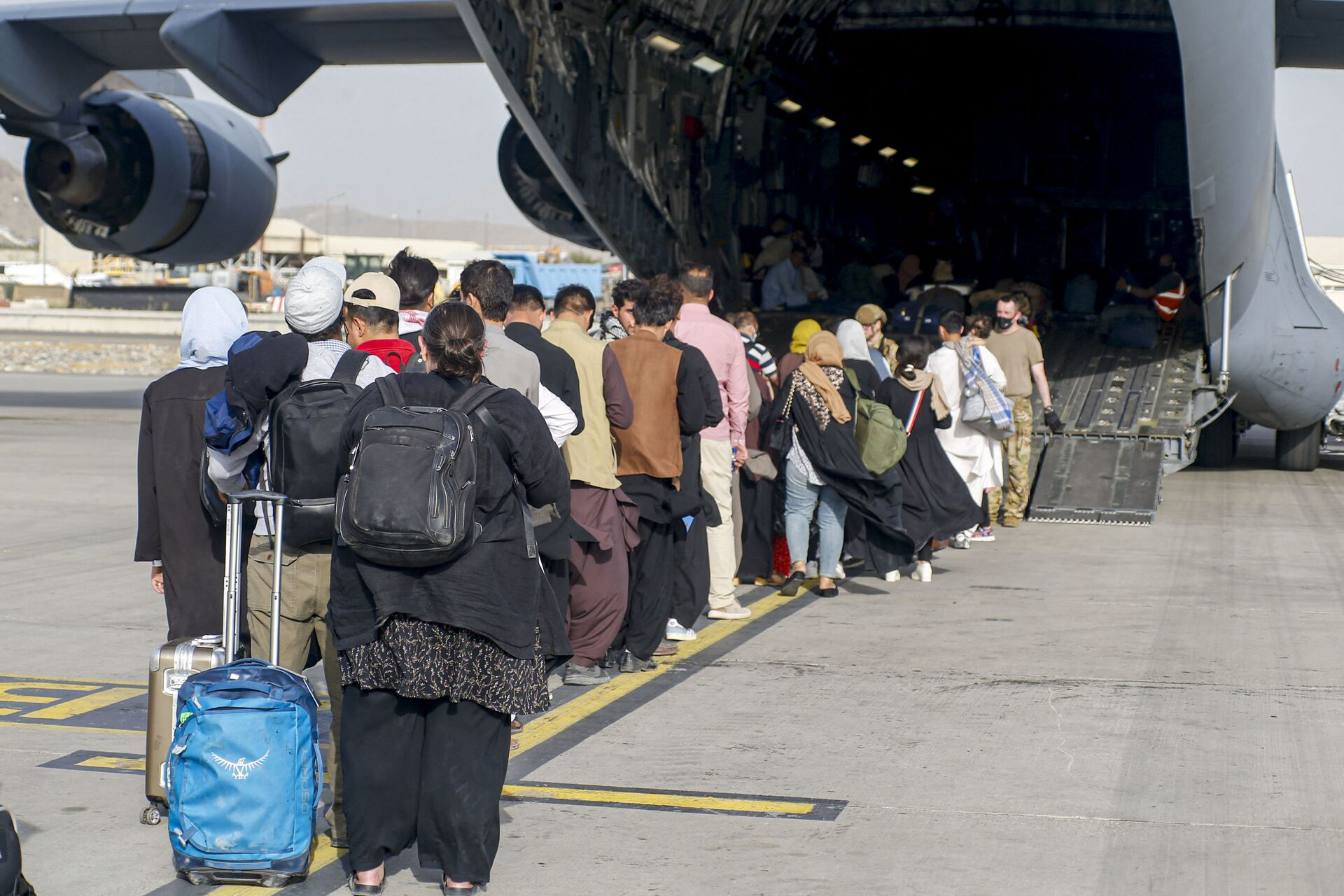 This handout photo courtesy of US Marines Corps shows evacuees stage before boarding a C-17 Globemaster III during an evacuation at Hamid Karzai International Airport, Kabul, Afghanistan, August 18, 2021 - Sputnik International, 1920, 07.09.2021