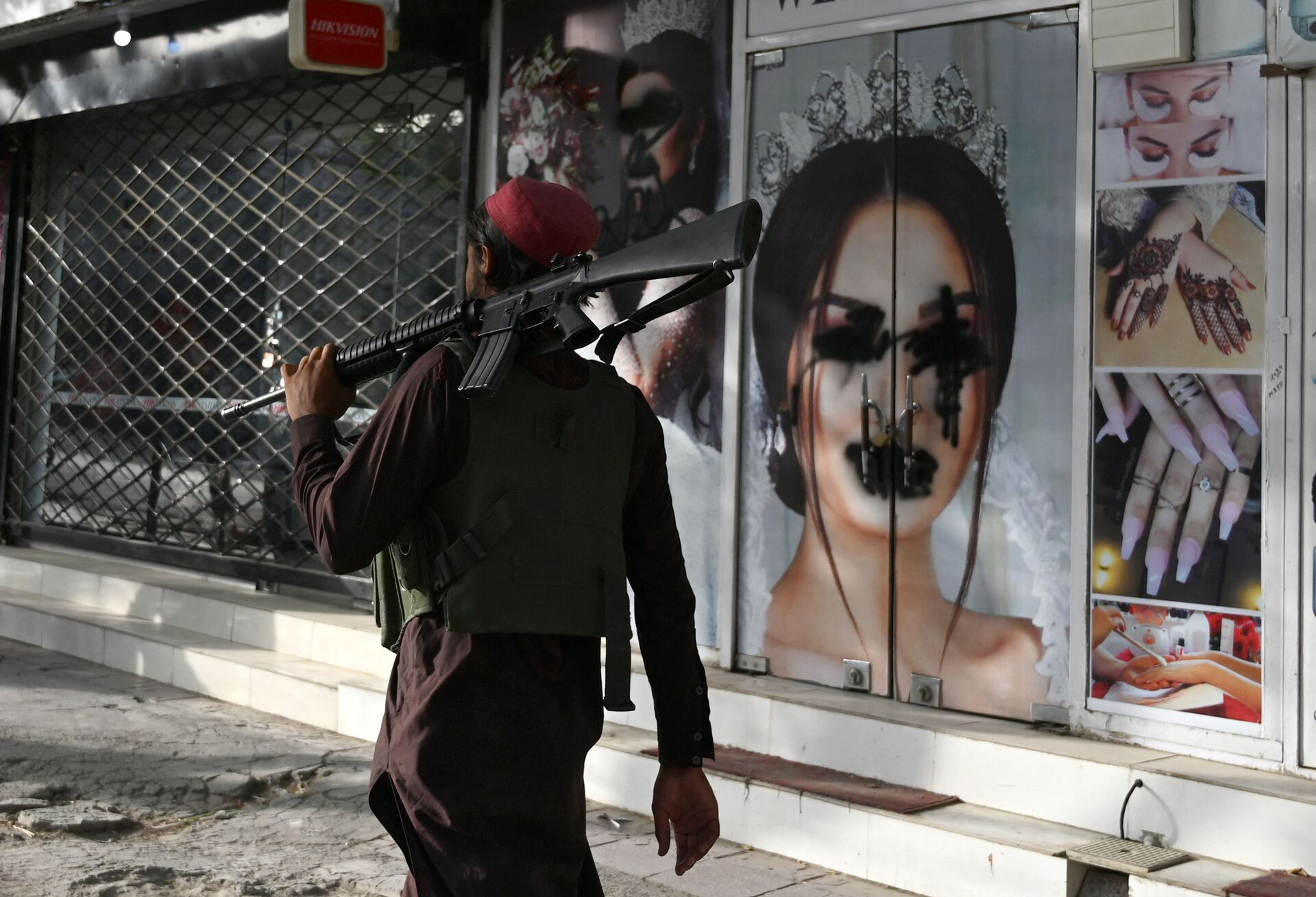 (FILES) In this file photo taken on August 18, 2021, a Taliban fighter walks past a beauty salon with images of women defaced using spray paint in Shar-e-Naw in Kabul - Sputnik International, 1920, 07.09.2021