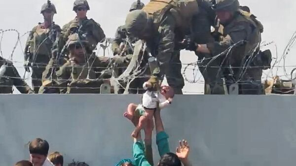 A baby is handed over to the American army over the perimeter wall of the airport for it to be evacuated, in Kabul, Afghanistan, August 19, 2021, in this still image taken from video obtained from social media. - Sputnik International