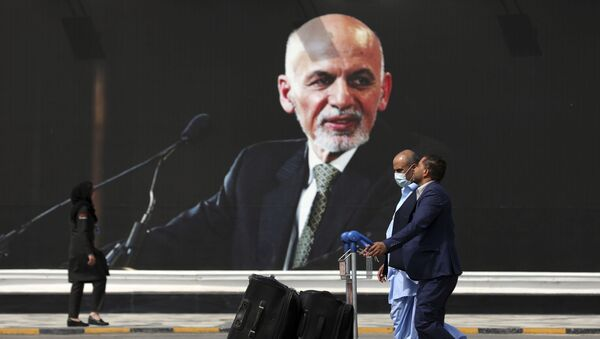 Passengers walk to the departures terminal of Hamid Karzai International Airport in Kabul, Afghanistan, on Saturday, Aug. 14, 2021, past a mural of President Ashraf Ghani, as the Taliban offensive encircled the capital. - Sputnik International