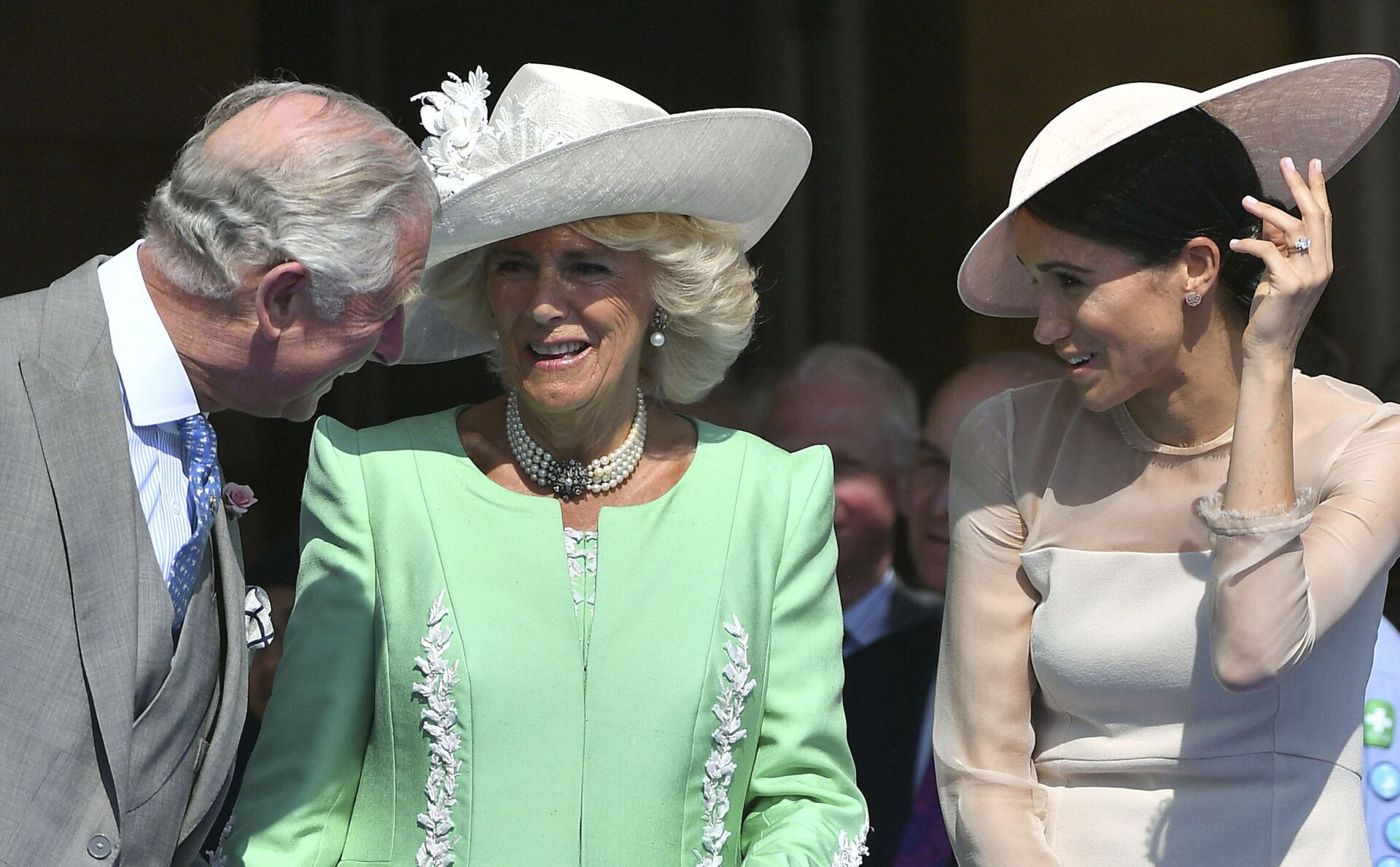 Britian's Prince Charles, left, reacts with Camilla, the Duchess of Cornwall and Meghan, the Duchess of Sussex, during a garden party at Buckingham Palace in London, Tuesday May 22, 2018. - Sputnik International, 1920, 07.09.2021