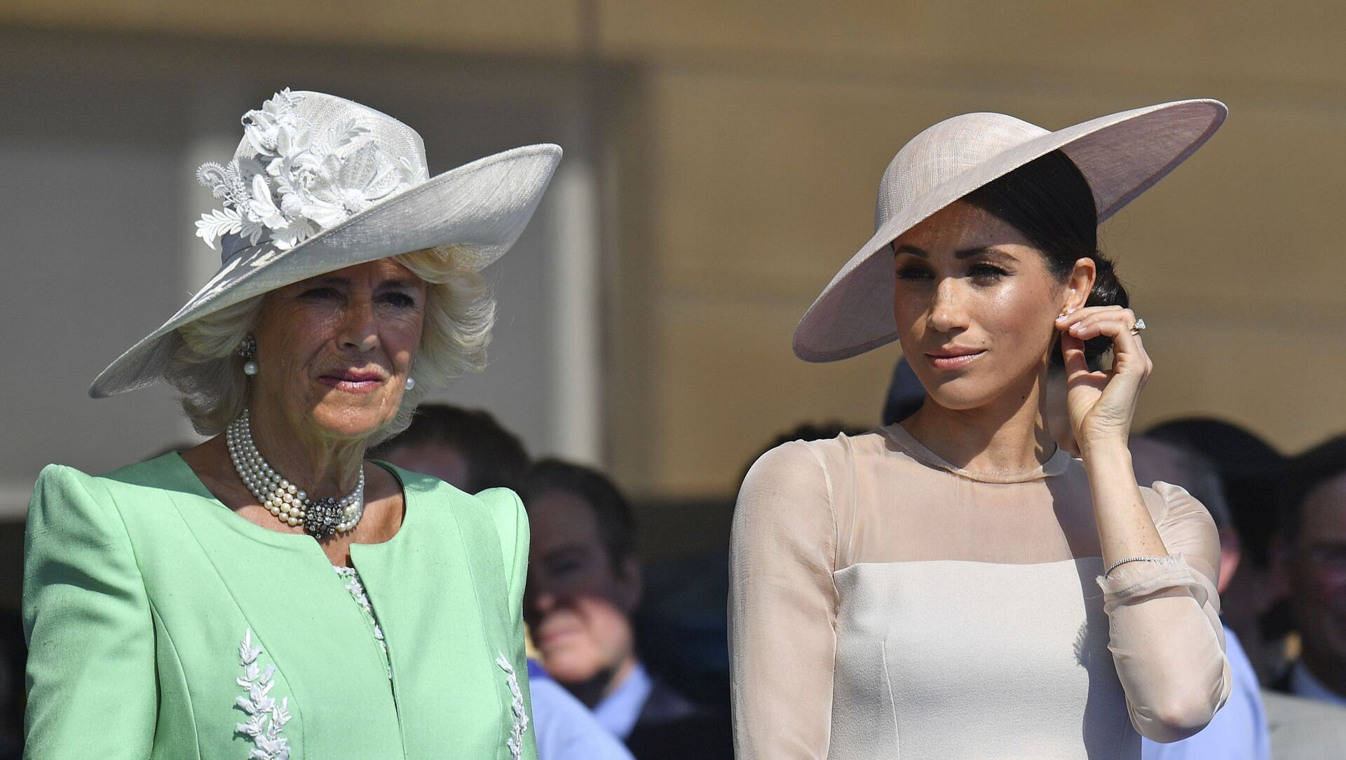 Meghan, the Duchess of Sussex, right, stands with Camilla, the Duchess of Cornwall, during a garden party at Buckingham Palace in London, Tuesday May 22, 2018. - Sputnik International, 1920, 22.08.2021