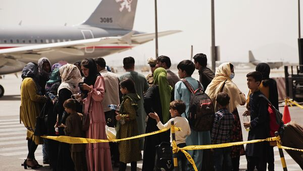 In this photo provided by the U.S. Marine Corps, civilians prepare to board a plane during an evacuation at Hamid Karzai International Airport, Kabul, Afghanistan, Wednesday, Aug. 18, 2021.  - Sputnik International