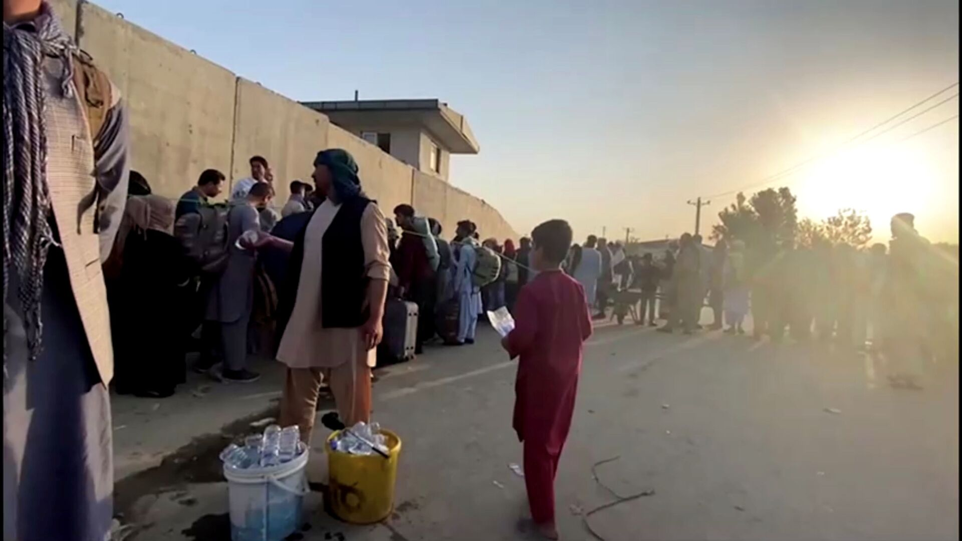 A man instructs people to queue as they stand with their belongings outside Kabul airport, Afghanistan, August 22, 2021 in this still image taken from video - Sputnik International, 1920, 07.09.2021