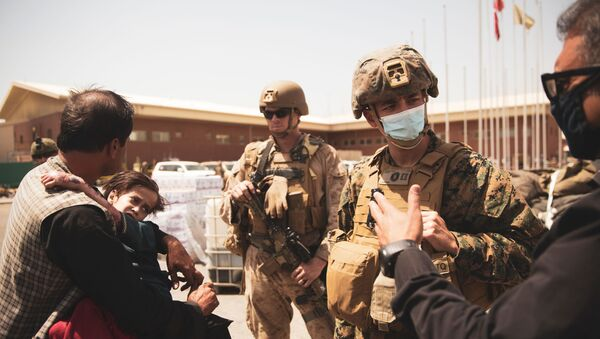 A U.S. Navy medical surgeon with the 24th Marine Expeditionary Unit (MEU) talks to an interpreter as he provides medical assistance to a family during an evacuation at Hamid Karzai International Airport, Kabul, Afghanistan, August 21, 2021. Picture taken August 21, 2021 - Sputnik International