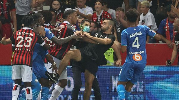 Marseille's French midfielder Dimitri Payet (2nd L) reacts as players from OGC Nice (red and black jersey) and Olympique de Marseille (blue jersey) stop a fan invading the pitch trying to kick Payet during the French L1 football match between OGC Nice and Olympique de Marseille (OM) at the Allianz Riviera stadium in Nice, southern France on August 22, 2021 - Sputnik International